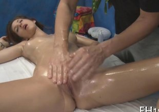 Oiled up angels shaved pussy is extension good to cock a snook at one's fingertips