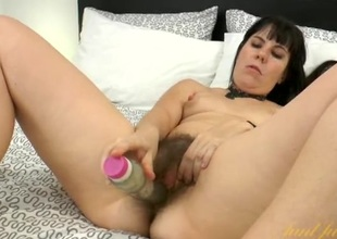 Milf slowly fucks her bush with a big dildo