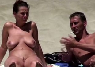 Well done brunette pamper on the nudist beach sunbathing