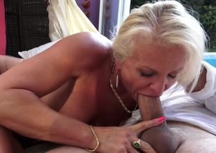 A granny with blonde seta is by the pool, possessions her wet pussy rammed