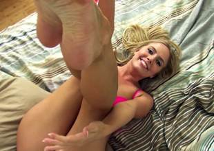 A blonde licks her black dildo while she is on the bed alone