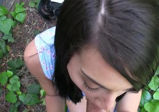 Dark haired sweetie sucks a chubby pecker outdoors for some initial