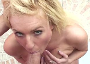 A blonde is displaying her large interior in the bathroom while sucking